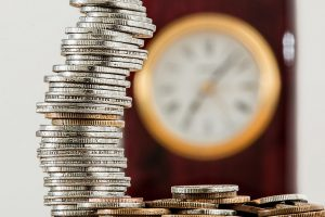 clock and stack of coins for an HSA or FSA