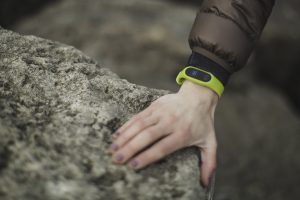 womans hand on a rock with a green tracker bracelet on her wrist
