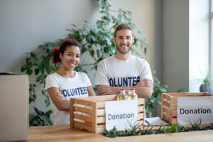 a man and woman with white shirts that say volunteer on them with a wodden box on a table that has a white sign with donation on it