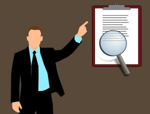 cartoon of a man in a suit pointing at a clipboard with magnifying glass over a certain part.