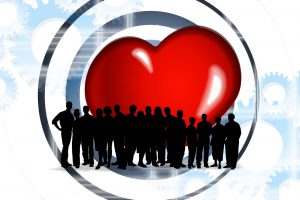 silhouette of a group of people with a huge red heart behind them in the background.