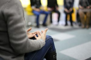 person sitting down in a circle with hands open.