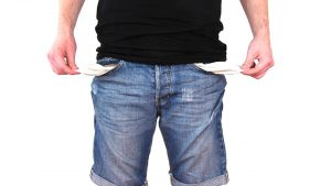 Man wit black shirt on and jeans, holding out empty jean pockets on both sides.