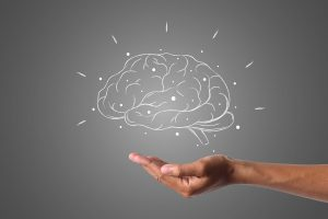 persons hand over a white drawing of a brain with a gray background.