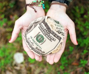 caucasian woman's hands with bracelets on wrists and a ball of cash in the middle of her open palms.