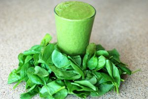 cup filled tot he top with green smoothie with spinach laying all around the cup.