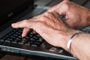 older caucasian hands typing on a laptop keyboard with a silver bracelet on one wrist.