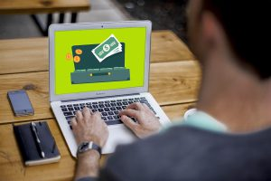 caucasian man sitting in front of a lptop with money going into a suitcase on the screen,