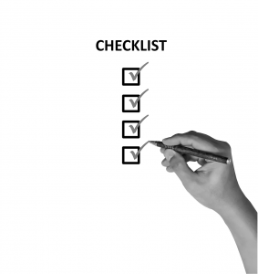 hand with pen checking off a checklist.