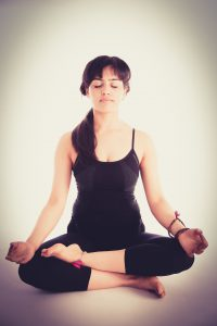caucasian woman in tank top and yoga capris sitting in a meditation position with hands on knees.