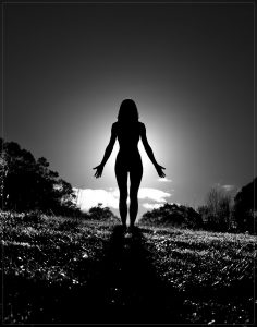 silhouette of a woman standing in mountain pose.