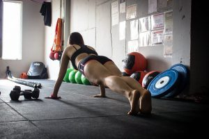 woman in a gym with sports bra and shorts doing a plank.