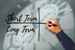 person drawing a cross with short term words over long term.