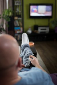 caucasian man laying on a couch with a remote in his hand with a blurred tv in the background.