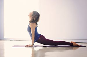 woman in workout clothes doing an upward dog.