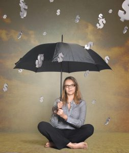 caucasian woman in business attire sitting under a black open umbrella with dollar signs coming down like rain.