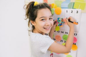little girl amiling with a pen in her hand in front of a calendar