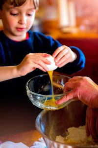 young caucasian boy breaking an egg into a bowl