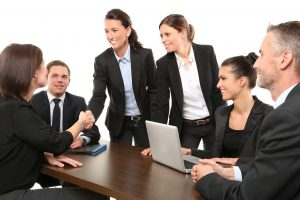 women and men in business suits sitting at a table, one woman standing up shaking the hand of a woman sitting down.