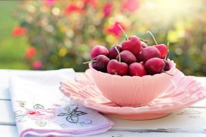 red cherries in a pink bowl.
