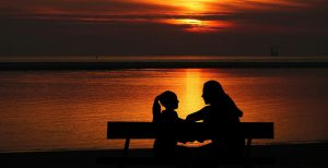 silhouette of a woman and an adolescent girl sitting on a bench facing each other with a sunset in the background.