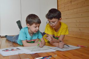 two little boys laying on their stomachs on the floor while coloring.