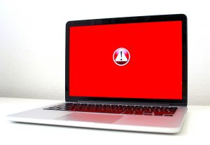 laptop screen that is red with a caution symbol in the middle.