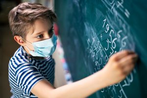 Caucasian boy with a mask on writing on the blackboard.