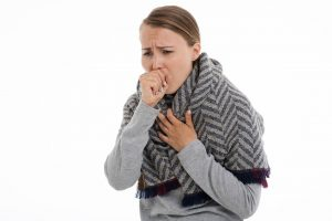 caucasian woman with scarf over her shoulders coughing into her right hand.