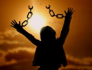 silhouette of a omwan with her hands in the air and broken chains