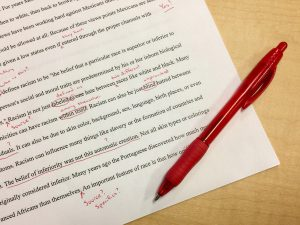 paper with red pen and marks all over writing