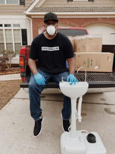 man with a mask on sitting on the back of a pickup truck touching a white sink.