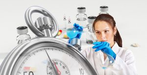 caucasian woman in a lab coat with gloves on mixing liquids with a stopwatch in front and vaccine bottles in the background.