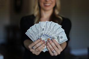 caucasian woman with blonde hair blurred in the backgroun holding 100 dollar bills in her hands