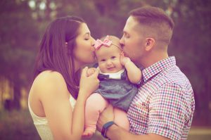 caucasian couple hlding a baby girl in the middle while both are kissing each cheek