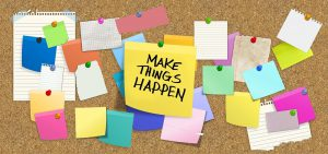 "bulletin board with many post notes and a big one in the middle that says ""make things happen"""