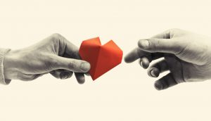one hand with a red paper heart giving it to another hand
