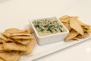 spinach artichoke dip in a bowl with chips around it