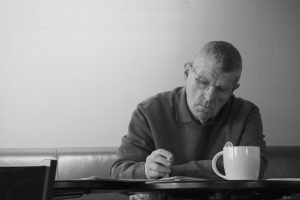 black and white picture of an older man sitting at a table with coffee mug and pen in his hand.