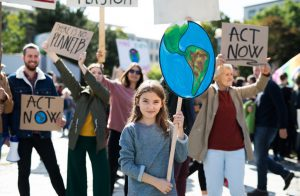 group of people with signs to act now against climate change