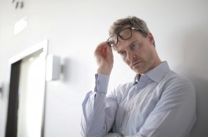 caucasian man with a white button up lifting his glasses above his eyed looking down