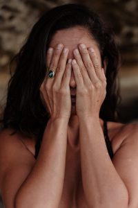 woman with her hands covering her face