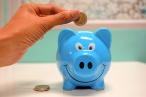 Caucasian hand holding a coin over a blue piggy bank