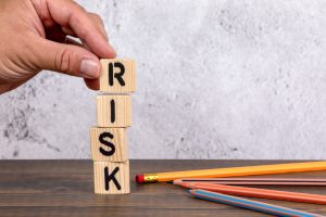 risk spelled out on wooden blocks with a hand on the R