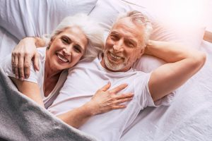 Caucasian older couple laying in bed together cuddling and smiling.