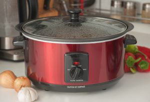 red crock pot with steam on the lid and veggies around it