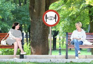 two caucasian women sitting on separate benches 6 ft apart with a sign in the middle that says 6 ft