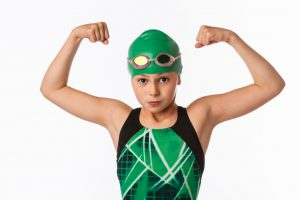 caucasian young girl wearing a green and black bathing suit, green swim cap and showing off her muscles.