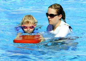 caucasian woman with glasses on and a whistle around her neck holding a water surfer with caucasian kid holding it.