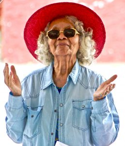 african american senior woman with a red sun hat on, jean shirt, and dark sunglasses on.
